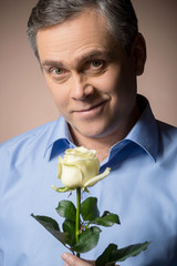man holding white rose and smiling.