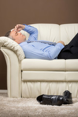 older businessman lying on white sofa.
