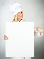 Female cook shows white blackboard with copyspace