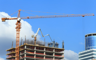 High-rise building under construction with crane, concrete pump.