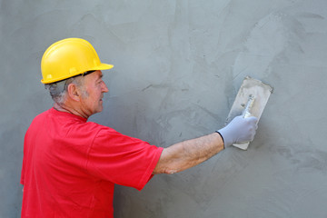 Worker making facade, trowel and cement mortar