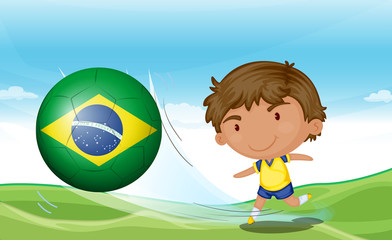 A boy beside the flag of Brazil