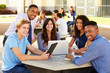 High School Students Working On Campus With Teacher