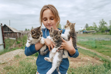 Smiling little girl holds cute kittens in summer outdoor
