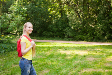 blonde girl with red rucksack  in the park at summer