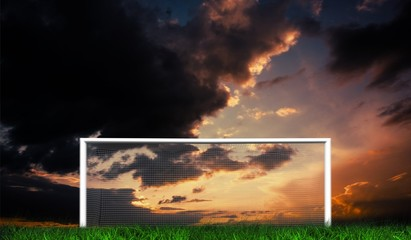 Football goal under sunset cloudy sky