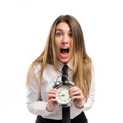 Young businesswoman holding an antique clock over white backgrou