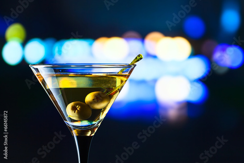glass with martini and green olives - 66145872