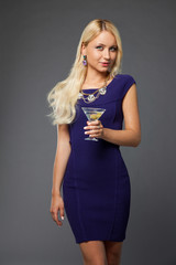 blonde girl wearing evening dress drinking martini