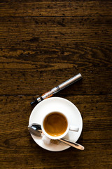 Cup of coffee and e-cigarette on a wooden counter