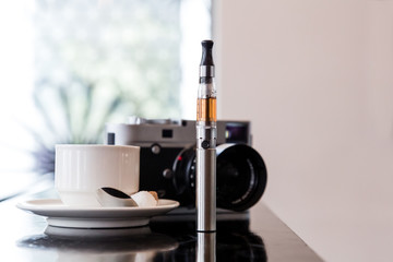 E-cigarette on a bar with coffee and a camera