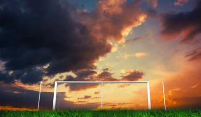 Football goal under orange cloudy sky