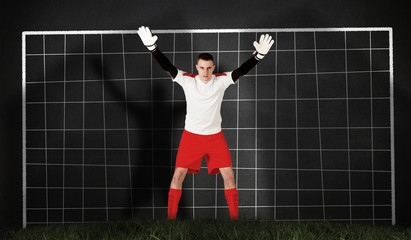 Composite image of goalkeeper in red and white ready to catch
