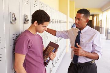 Male High School Student Talking To Teacher By Lockers