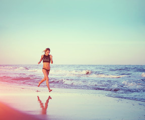 Beautiful female jogger runs along the sea, evening jog