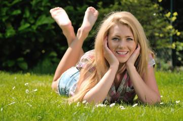 Junge hübsche Frau relaxt auf der Wiese