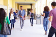 Group Of High School Students Walking Along Hallway - 66151053