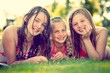 three girls smiling on a meadow
