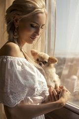 beautiful blond woman holding a small cute dog