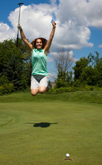 Woman jumping for joy as the golf ball heads into the cup