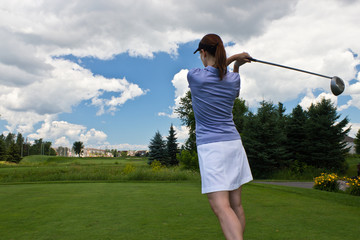 Female golfer swinging her golf club