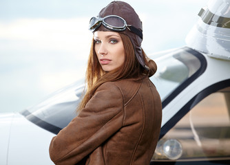 Portrait of young beautiful woman pilot in front of airplane.