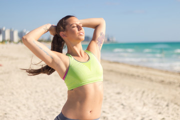 Fit hispanic woman stretches on the beach after a run