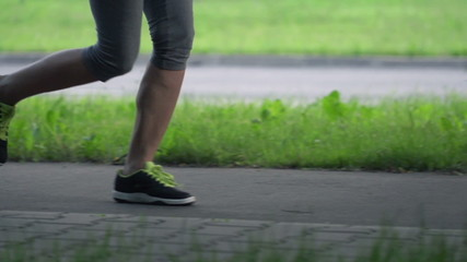 Woman legs jogging in the city, super slow motion