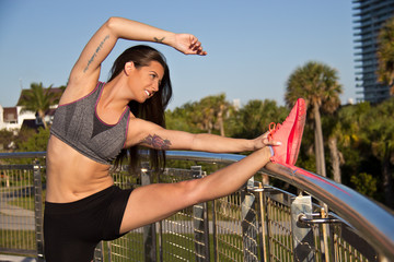 Beautiful hispanic woman stretching for fitness
