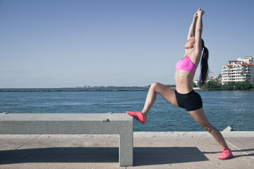 Fit woman stretching by the water