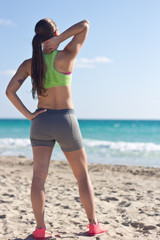 Fit woman relaxing after a run on the beach