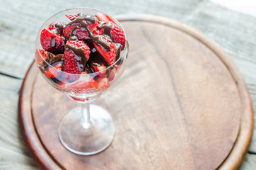 Fresh strawberries under chocolate topping in the glass