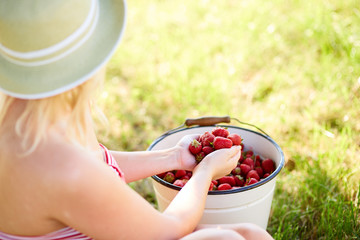 Woman sitting next to a bucket full of fresh strawberries