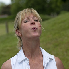 Portrait of a woman spitting out a cherry stone