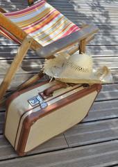 valise, chapeau et transat