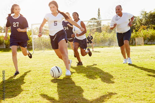 Members Of Female High School Soccer Playing Match - 66163413