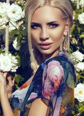sexy girl with blond hair posing beside a rose's bush