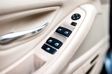 car leather interior details of door handle with window controls