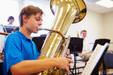 Fototapety Male Pupil Playing Tuba In High School Orchestra
