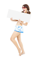 young girl wearing a swimwear  and holding a white board