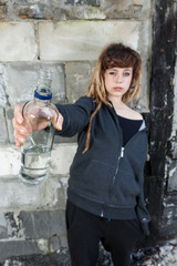Young girl with bottle of vodka