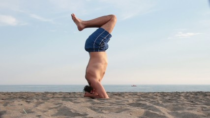 man doing Yoga on the beach , sirsana