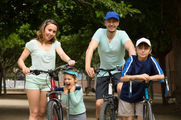 Smiling family of four with bicycles and scooter