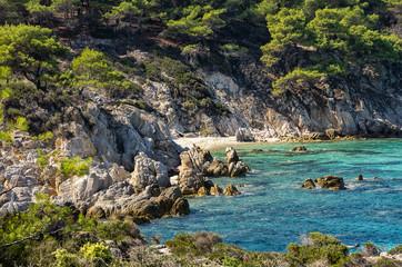 Rocky coast with a hidden sandy beach in Chalkidiki, Greece