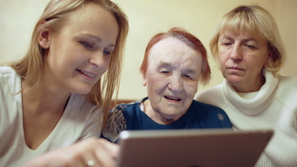 Woman with pad showing photos or video to her mother and