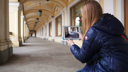 Woman with tablet PC making photo of hall in perspective