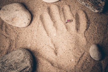 Ring and hand print in sand