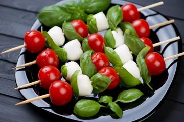 Kebabs with mozzarella balls, red tomatoes and green basil