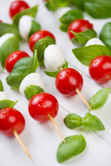 Mozzarella balls and cherry tomatoes with green basil on skewers