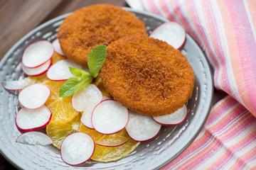 Fried salmon cakes with sliced orange and radish, studio shot